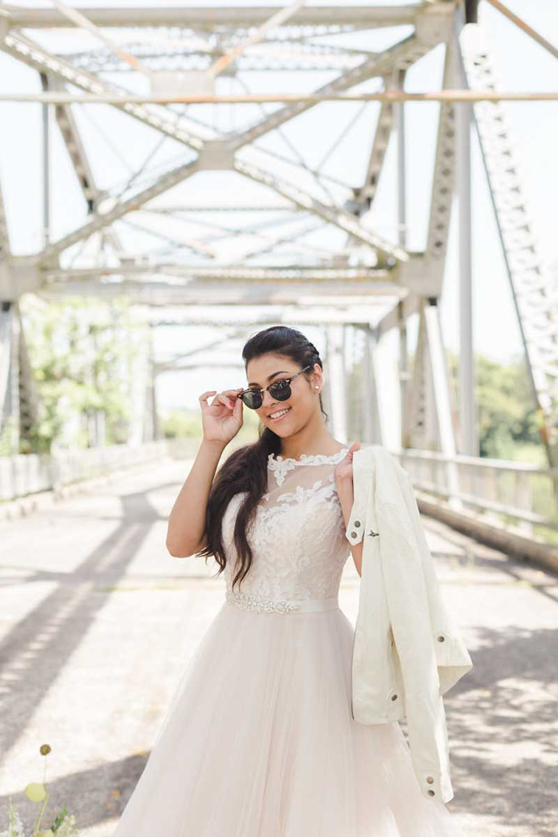 bride holding jacket over shoulder and tipping sunglasses