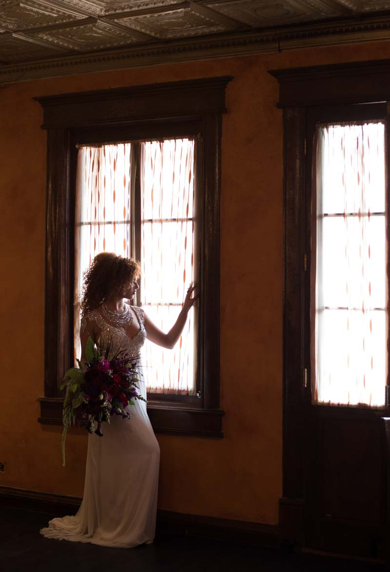 bride holding bouquet looking out window