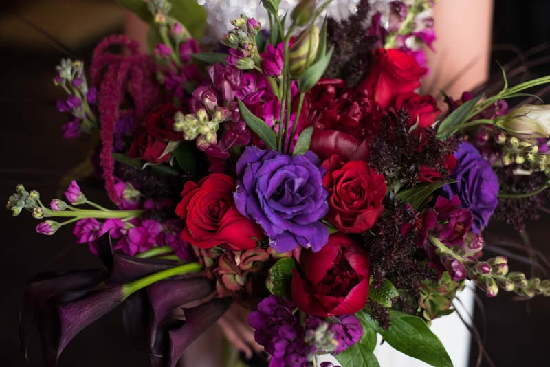 bride holding deep purple and red bridal bouquet