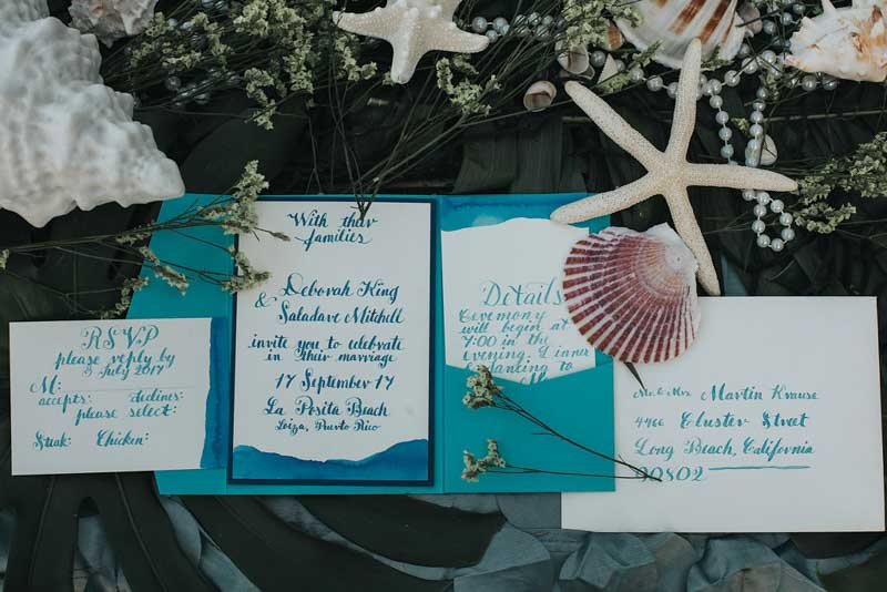 blue and teal calligraphy wedding invitations surrounded by seashells