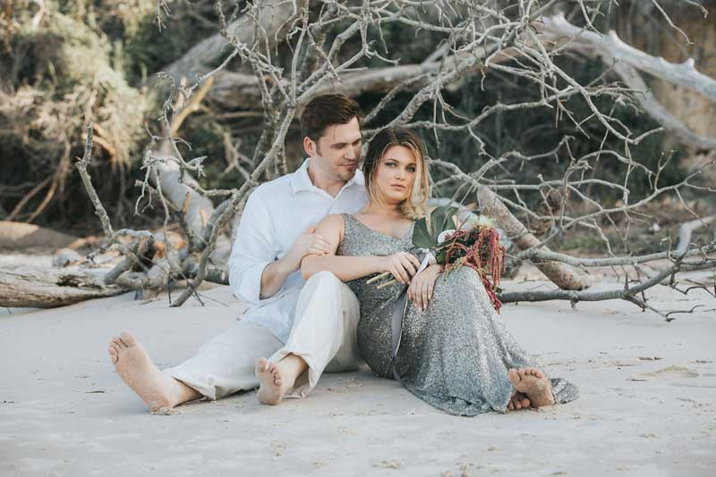 bride and groom sitting in sand for mermaid elopement inspiration shoot