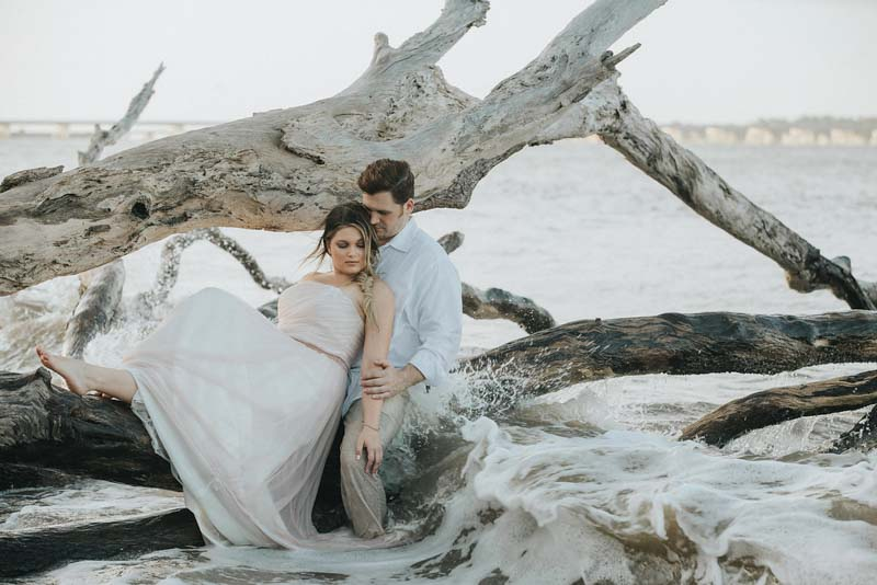 bride and groom sitting on driftwood
