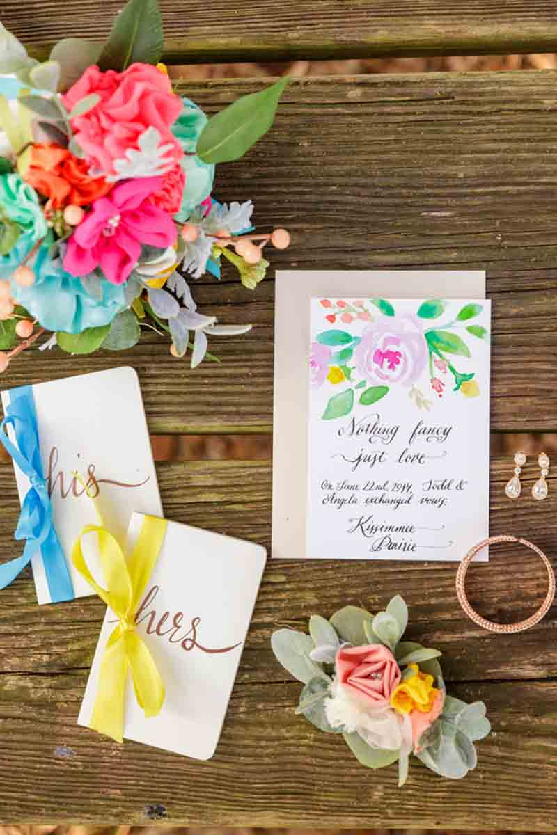 watercolor invitation and vow books on wood table