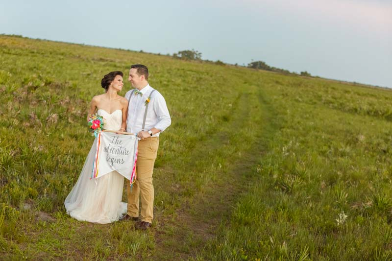 couple holding the adventure begins sign