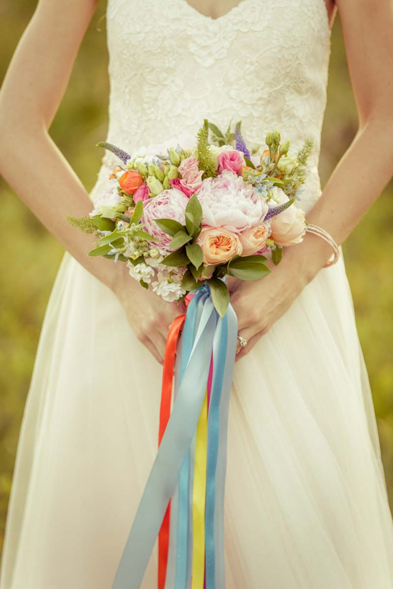 bride holding blush and orange bridal bouquet