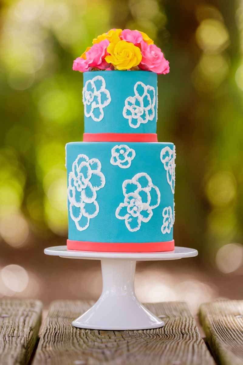 blue wedding cake with white flowers on white cake stand