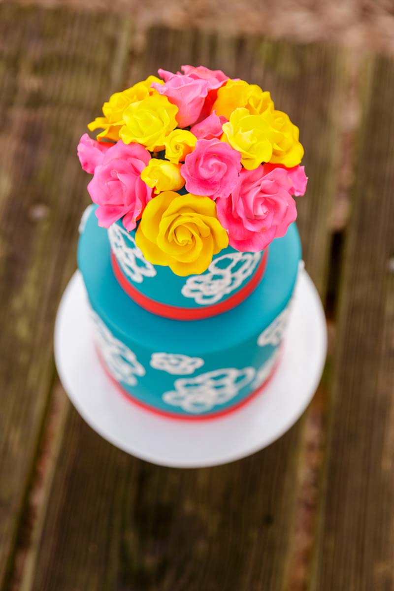 yellow and pink sugar flowers on blue cake