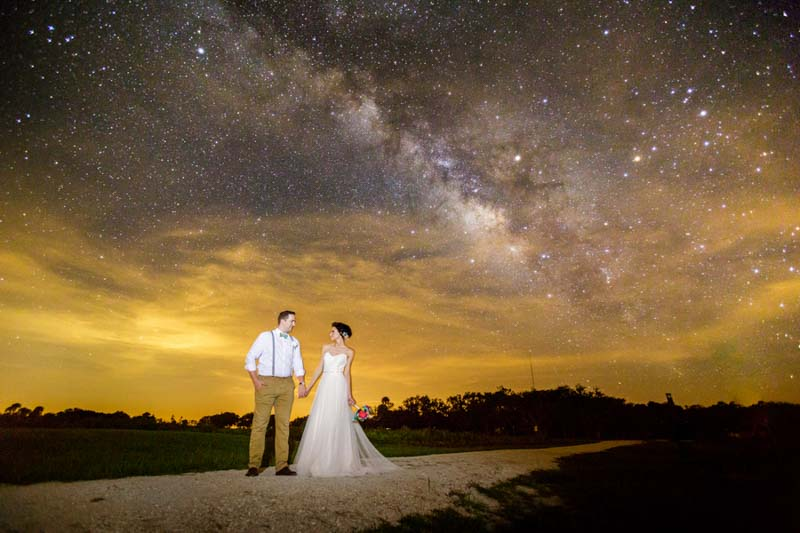bride and groom holding hands under the milky way