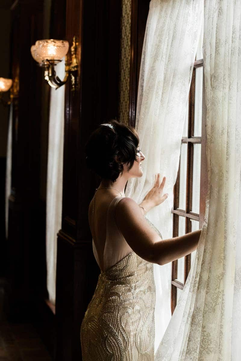 bride looking out window in bridal gown