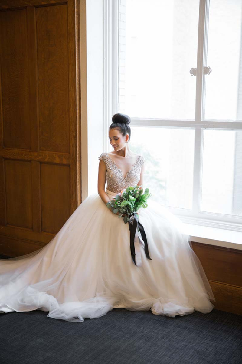 bride sitting on window sill holding bouquet