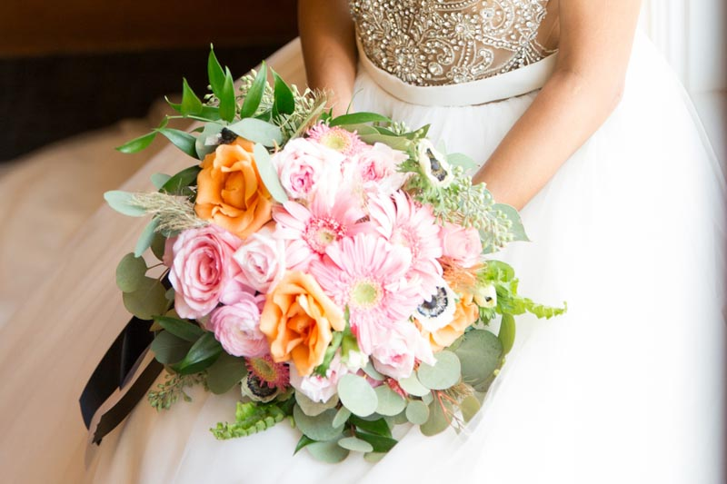 bride holding pink and orange bouquet