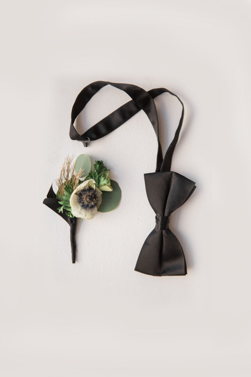 black bowtie next to boutonniere
