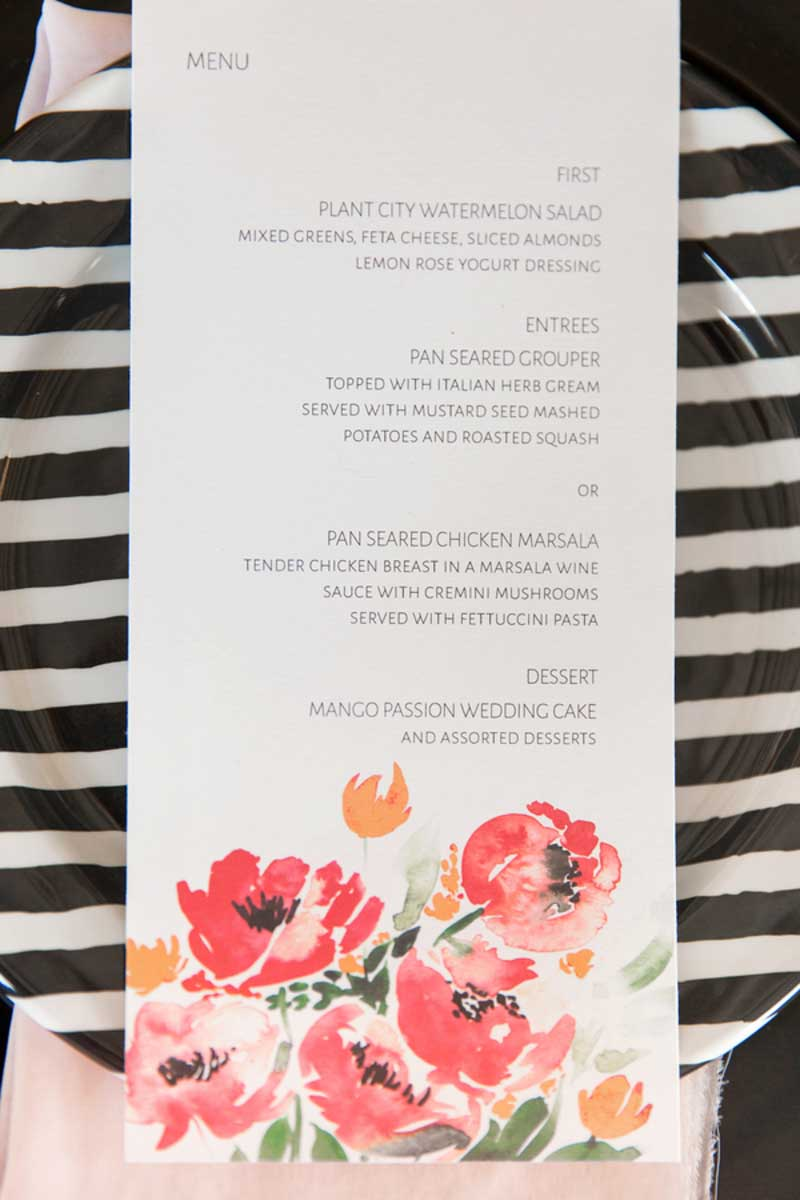 watercolor menu card laying on black and white plate
