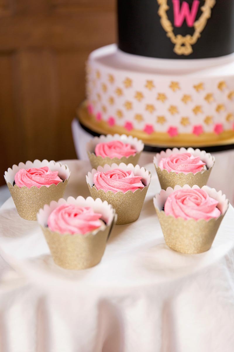 pink frosting cupcakes next to wedding cake