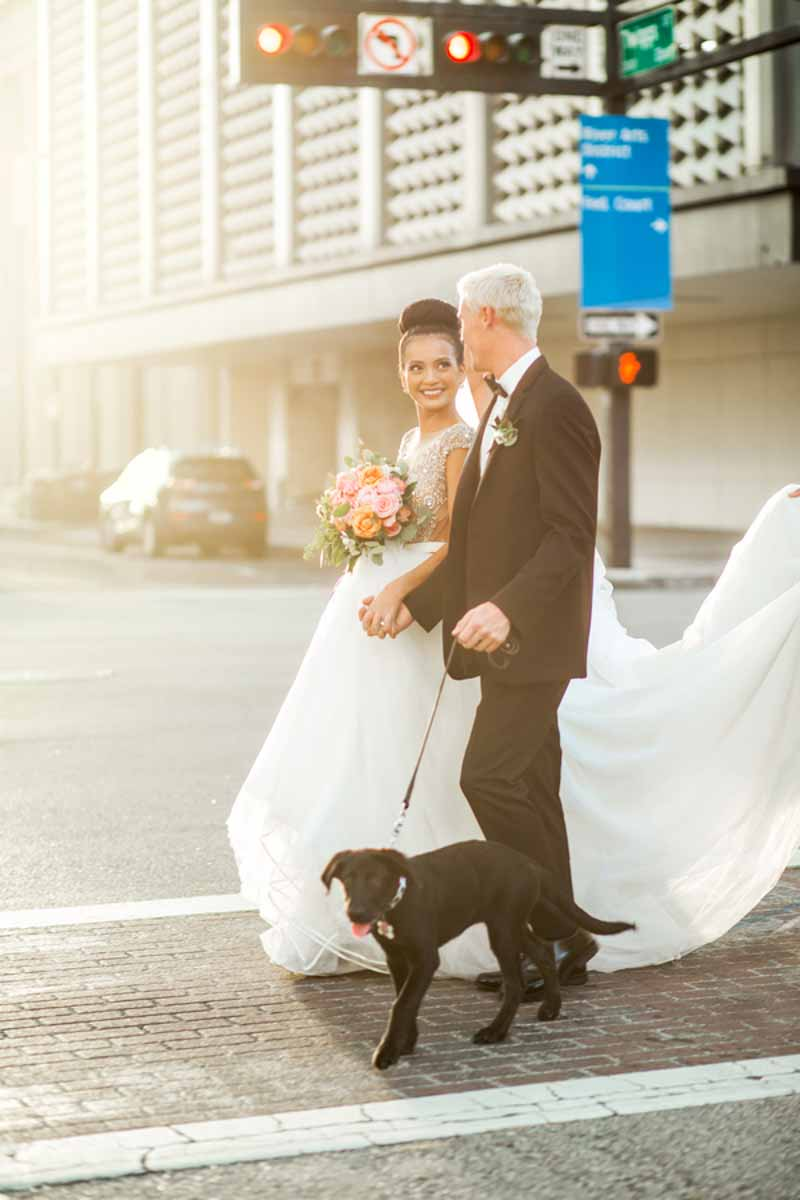 bride and groom walking puppy across street