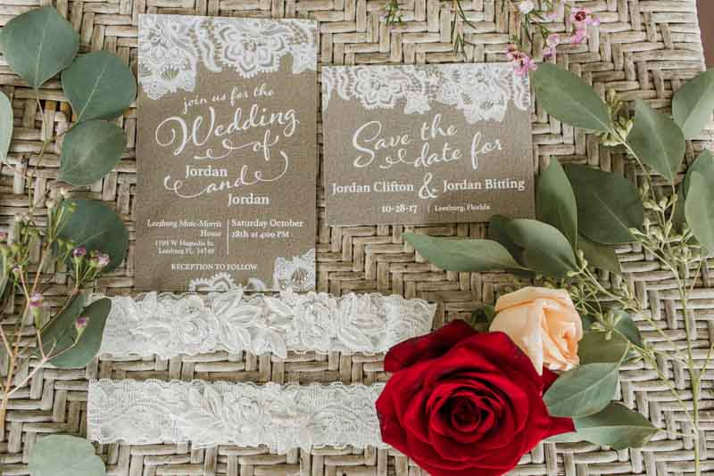 taupe wedding invitations on basket next to lace garter