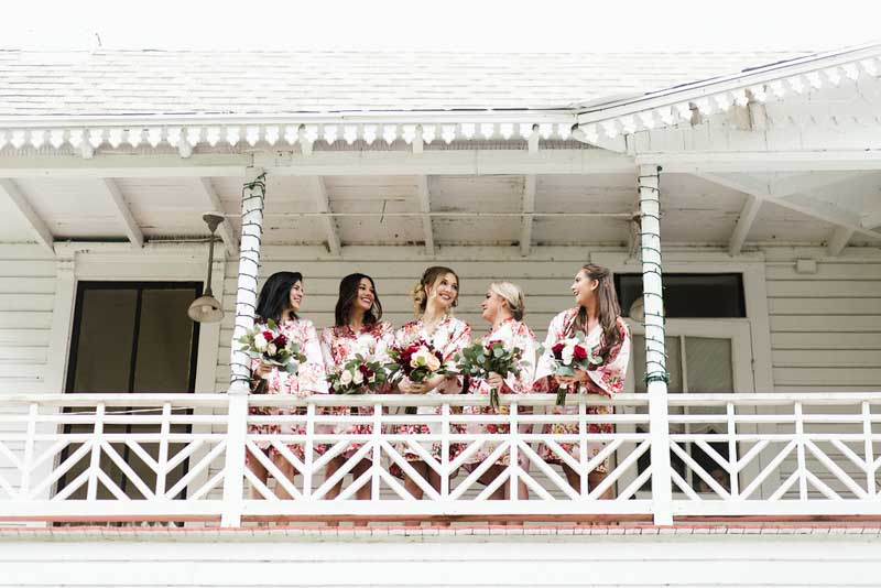 bride and bridesmaids in floral robes on balcony