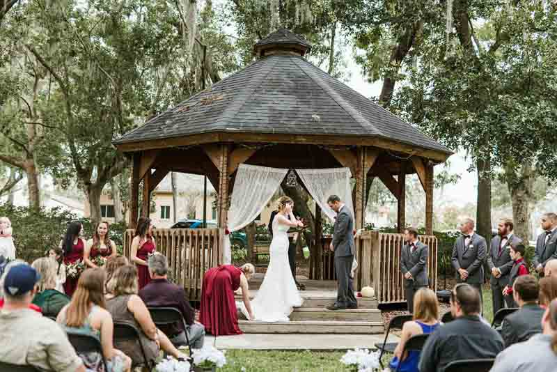 bride and groom standing in front of gazebo for wedding ceremony
