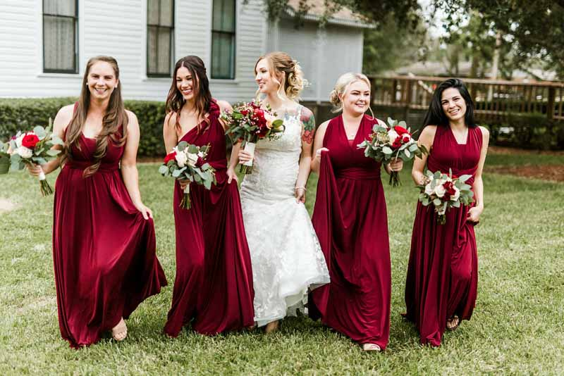 bridesmaids in burgundy dresses holding bouquets