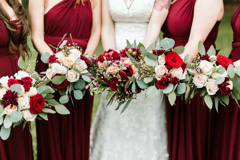 bride and bridesmaids holding burgundy and blush bouquets