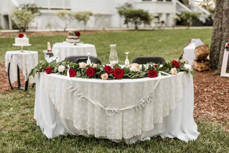sweetheart table with red rose garland across