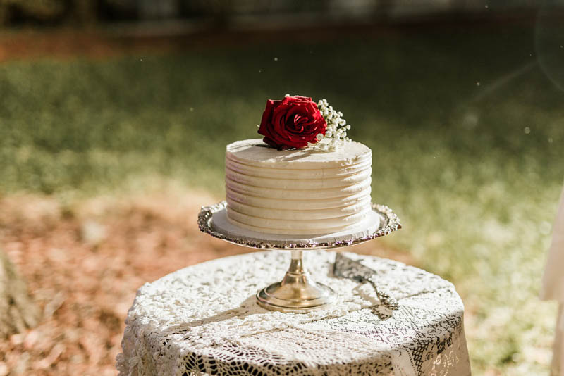 white buttercream wedding cake with red rose on top