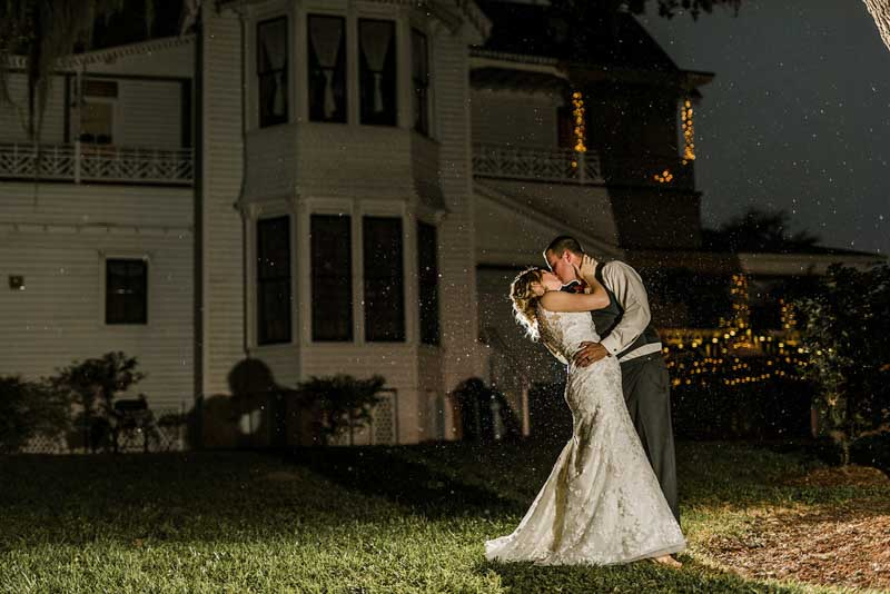 bride and groom kissing at night in front of the Mote-Morris House