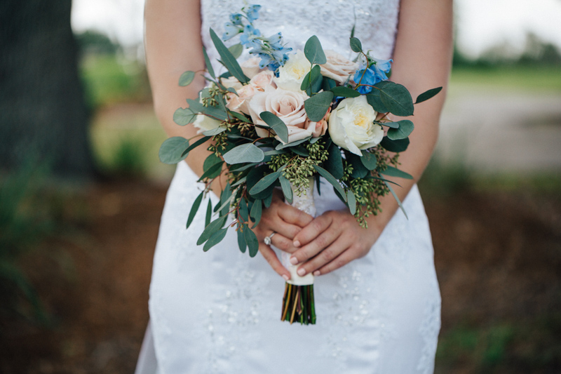 bride holding blush and white rose bouquet