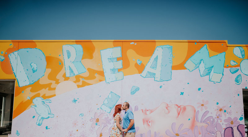 Couple kissing in front of Children's Dream Fund Mural