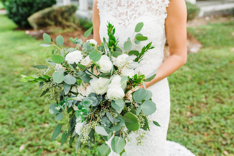 bride holding greenery and white bridal bouquet