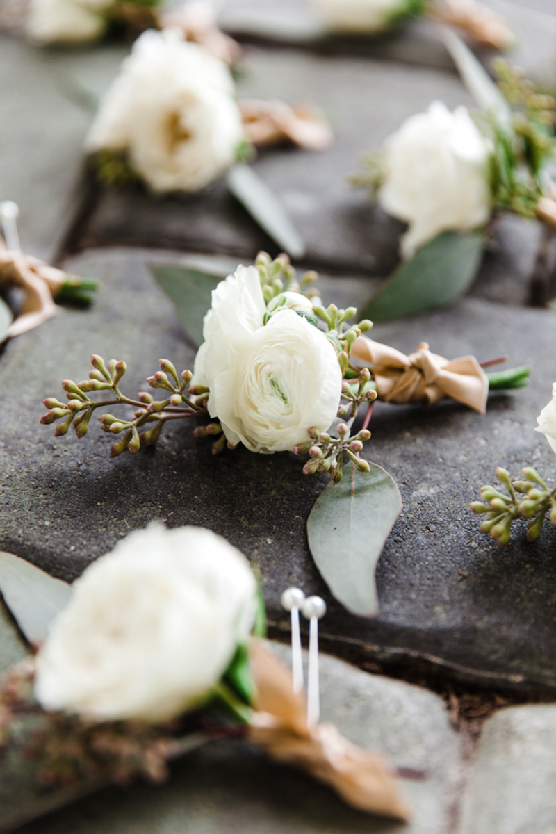 white boutonnieres on cobblestone walkway