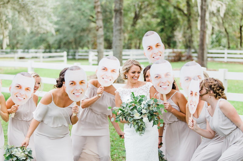 bridesmaids holding faces of groom