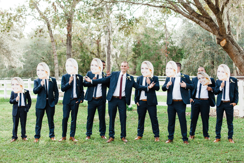 groomsmen holding faces of bride