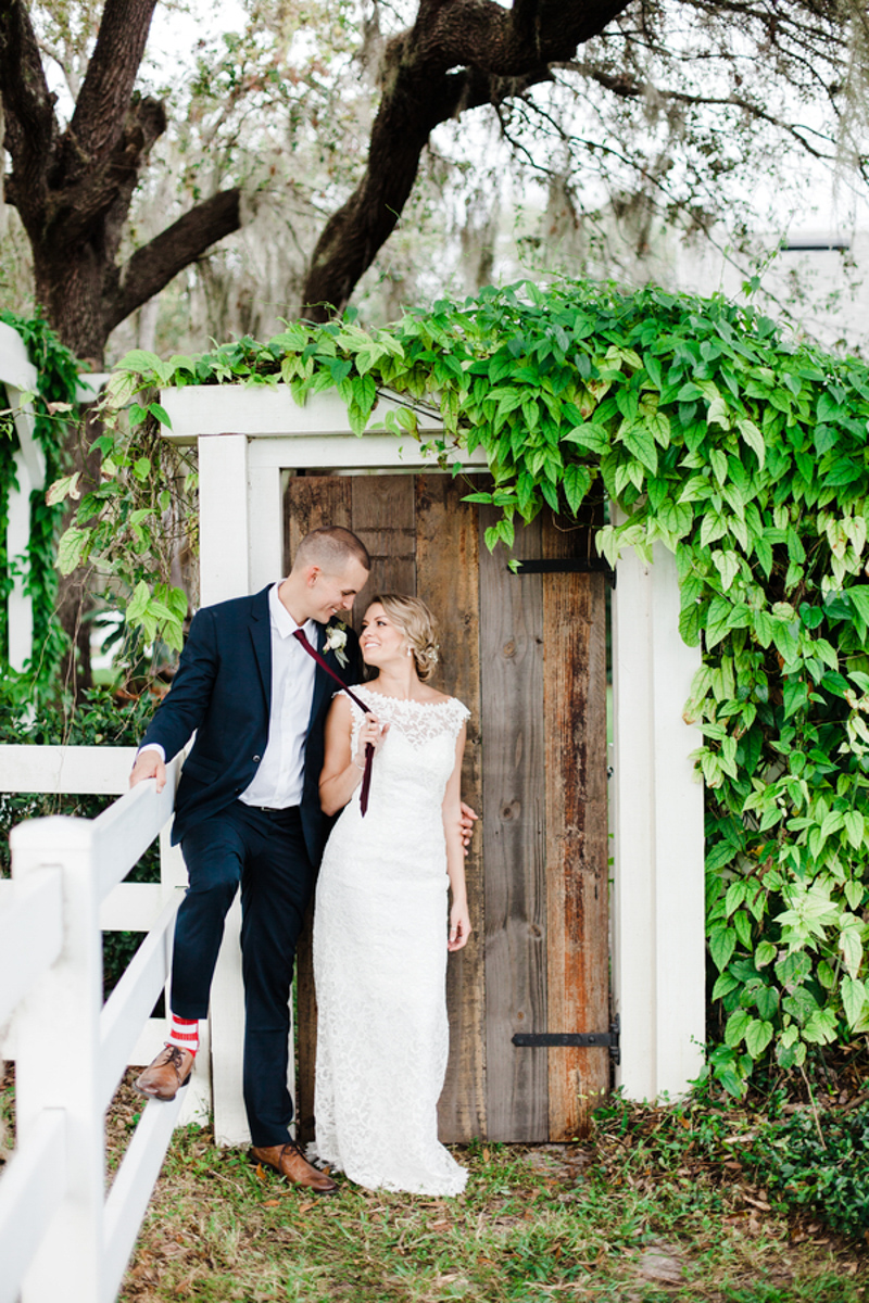 bride and groom standing in front of rustic door for Bramble Tree Estate wedding