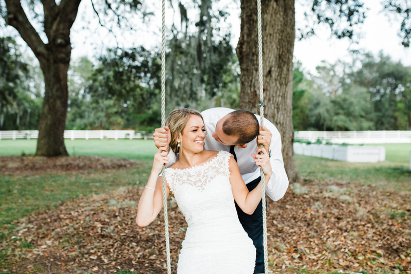 groom pushing bride on tree swing