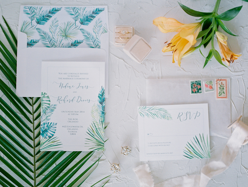 tropical wedding invitation suite laying on white backdrop