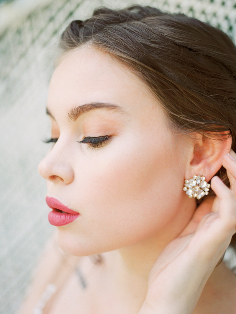 bride holding hair back to show diamond cluster earrings