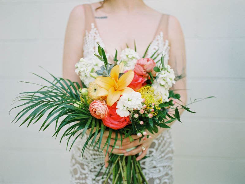 bride holding tropical wedding bouquet by Fern and Curl Designs