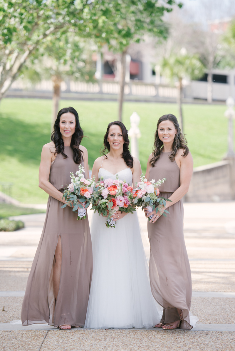 bridesmaids in taupe dresses next to bride