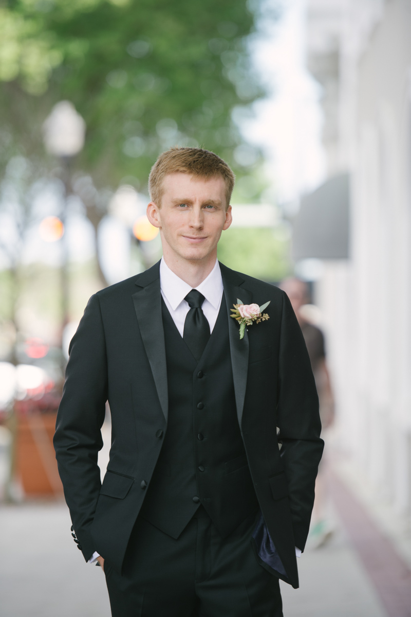 groom in black tax with pink boutonniere