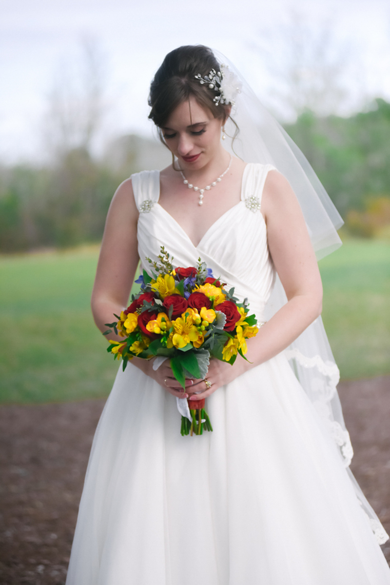 bride looking down at yellow and red bouquet