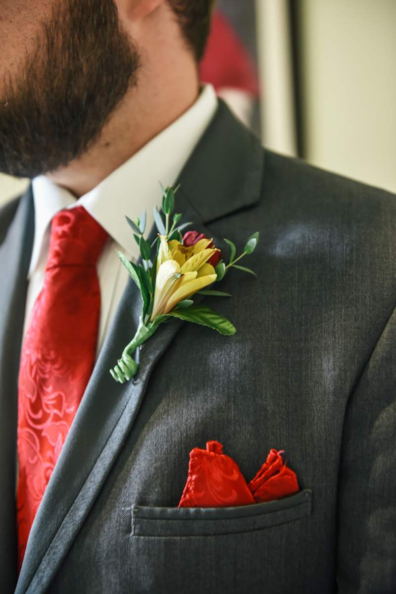 yellow and red boutonniere on grey suit