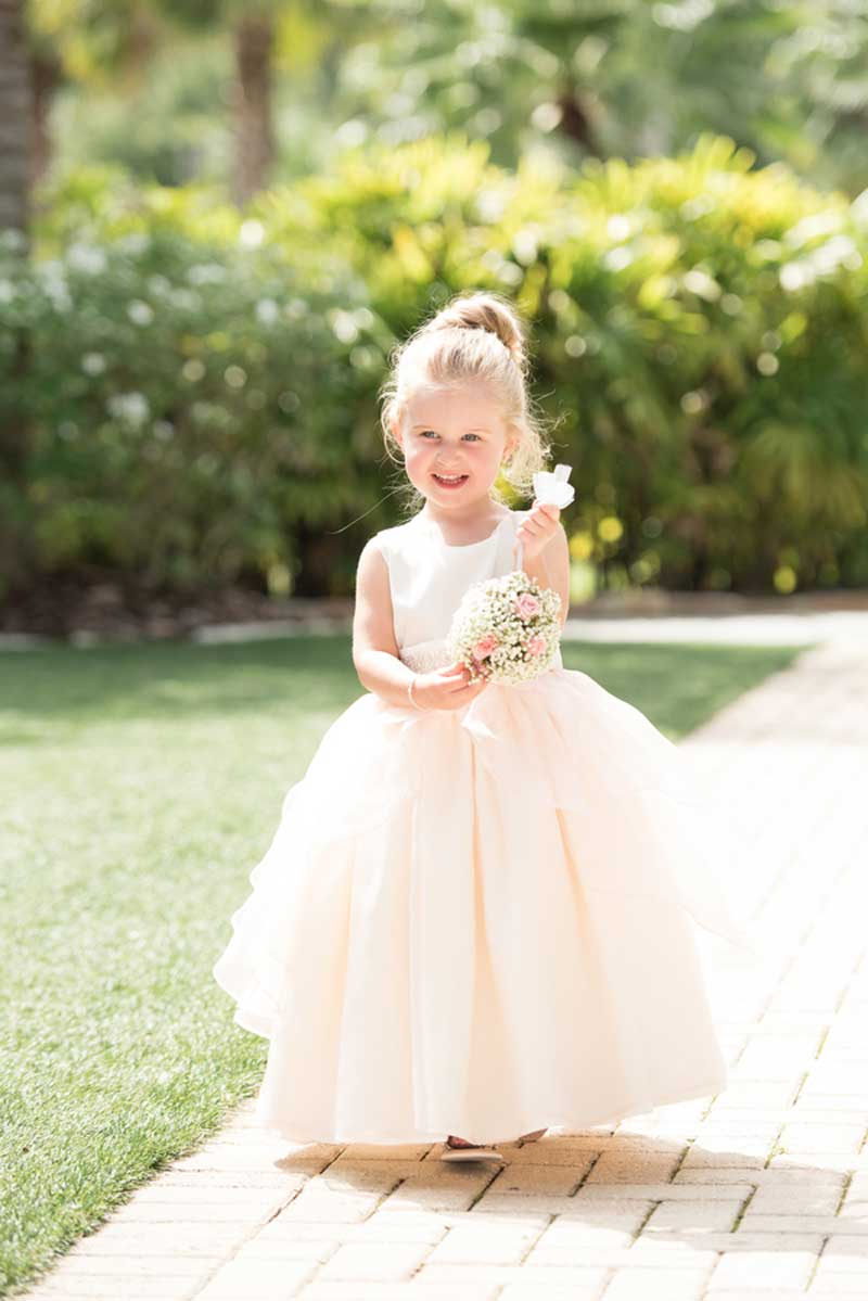 flower girl walking up the aisle in blush dress