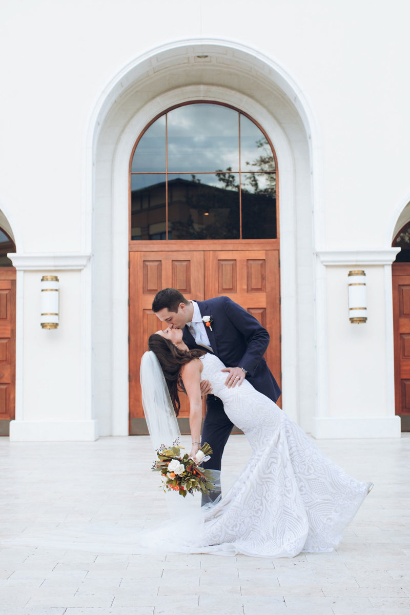 bride and groom kissing in front of St. Margaret Mary's Catholic Church