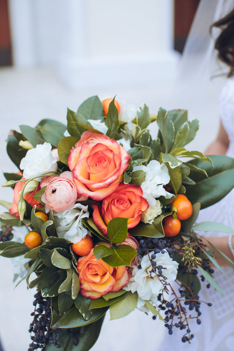 bride holding orange rose bouquet by Weddings by Carly ane's