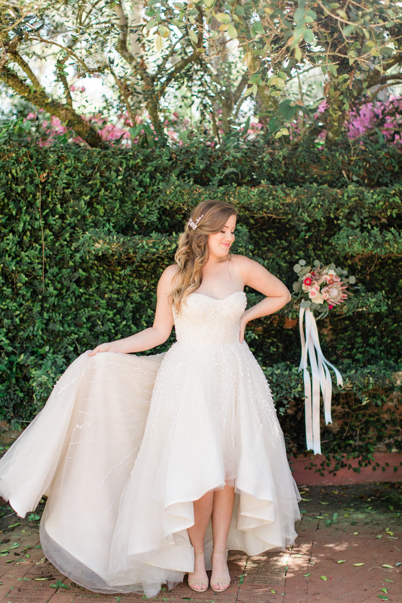 bride in front of hedge wall holding Anne Barge wedding gown