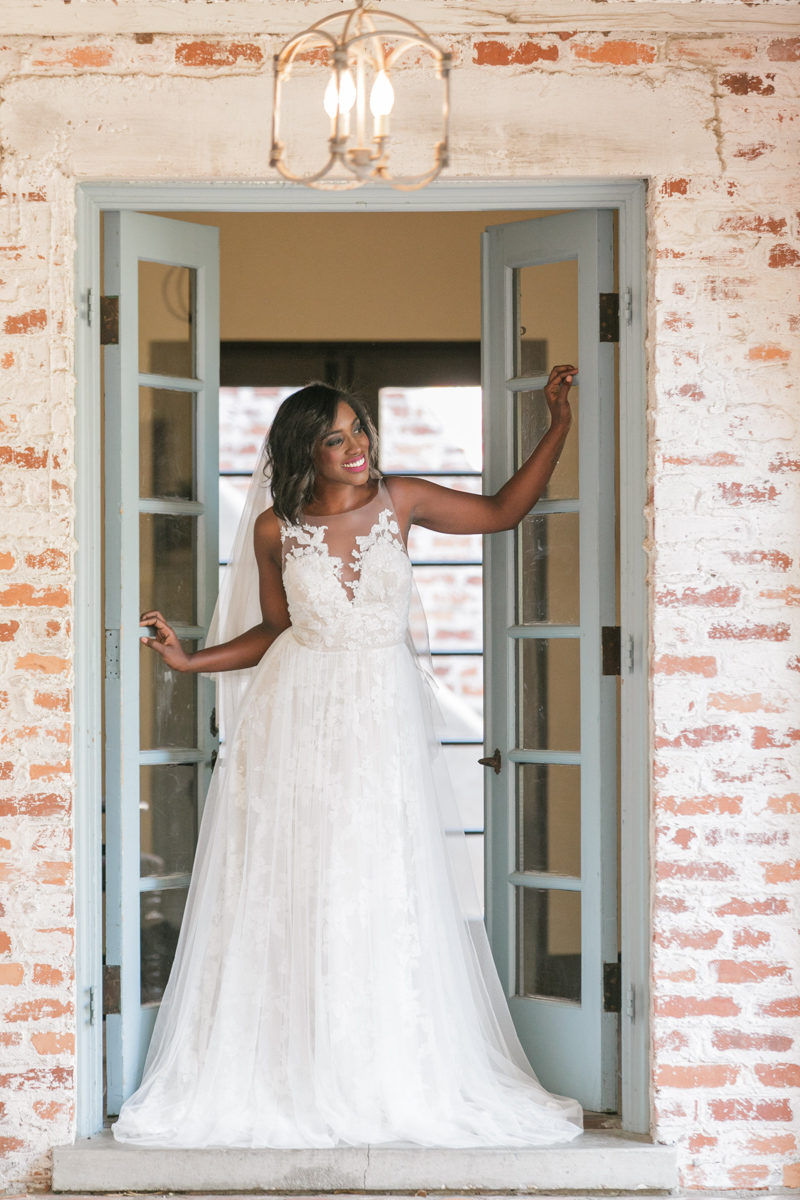 bride looking out doorway in Theia Couture wedding gown