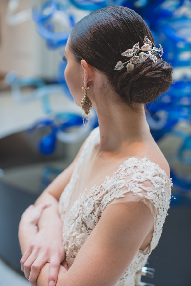 Bride wearing low updo with hairpiece by Maria Elena Headpieces