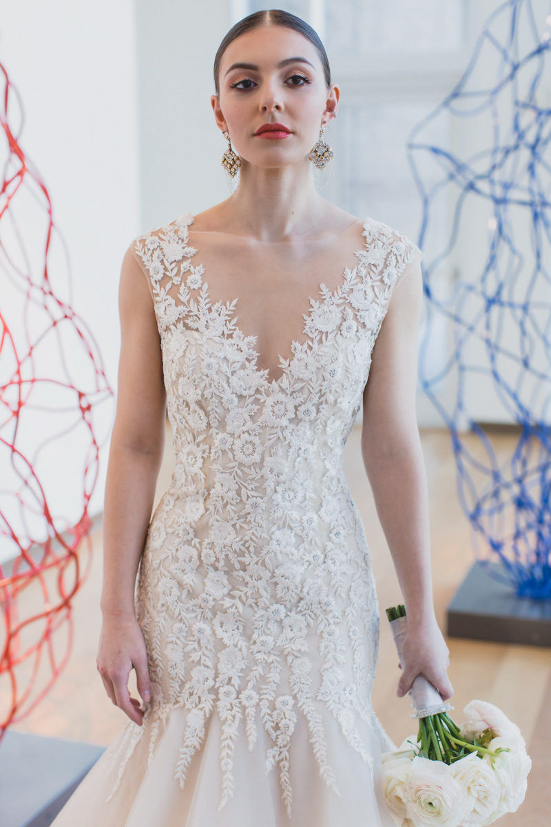 Bride wearing mermaid Monique Lhuillier wedding dress next to wire sculptures