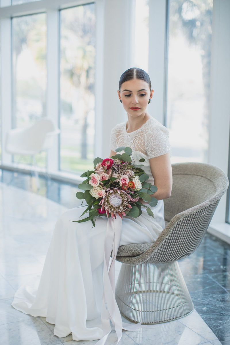 bride in chair wearing beaded Jenny Packham wedding dress